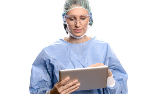 entering information: Attractive female doctor or surgeon in scrubs and a surgical gown, goggles and cap entering patient information on a tablet computer, isolated on white