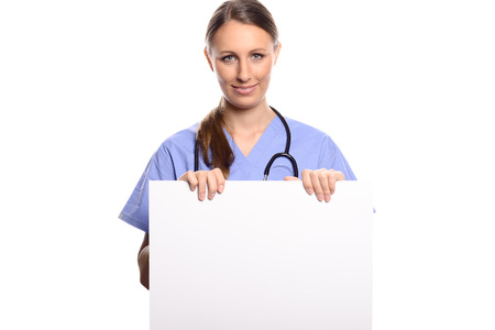 Attractive young female doctor, veterinarian or nurse holding a blank white placard in her hands with copy space for your text or advertising, isolated on white photo