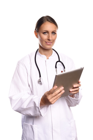 Attractive female nurse or doctor in a white gown standing consulting a tablet computer reading the information with a friendly expression, isolated on white photo