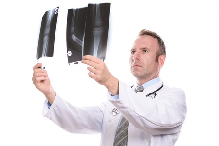 paediatrics: Male doctor, radiologist or orthopaedic surgeon comparing two x-rays holding them up to the light, isolated on white