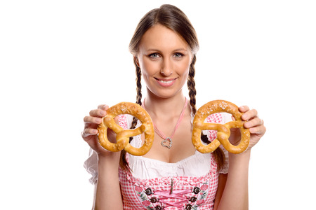 German or Bavarian waitress with her hair in pigtails wearing a traditional dirndl holding two fresh pretzel , Oktoberfest concept isolated on white