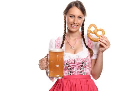trenzas en el cabello: Una sonrisa hermosa mujer joven con el pelo trenzado en un dirndl rojo alem�n o b�varo tradicional que sostiene una jarra de cerveza vaso de cerveza y pretzel, Oktoberfest conceptual de aislados en blanco Foto de archivo