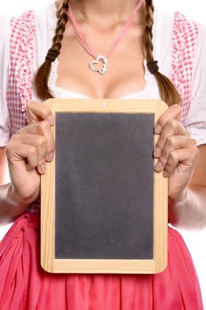 comida alemana: Mujer joven en un dirndl sosteniendo una pizarra en blanco la escuela de época frente a su pecho con copyspace para su publicidad, de menú o de prueba, vista de cerca el torso Foto de archivo