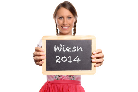 wiesn: Young woman in a dirndl holding up a blank vintage school slate in front of her chest with wiesn 2014 written on it, close up torso view