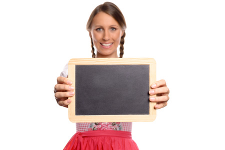 dirndl: Young woman in a dirndl holding up a blank vintage school slate in front of her chest with copyspace for your advertising , menu or test, close up torso view Stock Photo