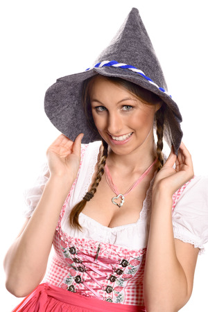 Beautiful happy young woman with her hair in plaits wearing a traditional German dirndl and rustic hat smiling up at the camera, isolated on white photo