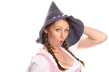 jaunty: Mujer atractiva en un dirndl alem�n o b�varo tradicional y sombrero de fiesta r�stica adoptando una pose seductora alegre como ella mira a la c�mara con una mueca, aislado en blanco