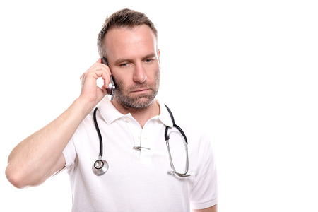 Middle-aged male doctor in a white shirt and stethoscope taking a call on his mobile phone with a serious expression as he listens to the conversation, isolated on white photo