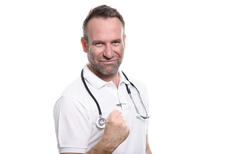 Enthusiastic unshaven middle-aged doctor punching the air with his fist celebrating a successful treatment or prognosis with a look of jubilation and glee, isolated on white