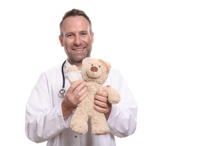 paediatrician: Friendly smiling middle-aged male pediatrician with unshaven stubble holding a teddy bear