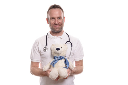 seeks: Smiling caring paediatricain or male paediatric nurse holding a cute stuffed teddy bear as he seeks to comfort and reassure a young patient on the hospital ward, isolated on white Stock Photo