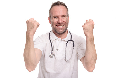 jubilation: Enthusiastic unshaven middle-aged doctor punching the air with his fist celebrating a successful treatment or prognosis with a look of jubilation and glee, isolated on white
