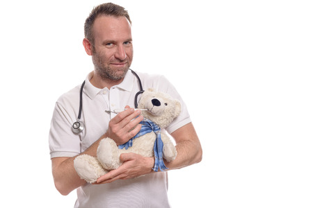 reassure: Smiling unshaven caring pediatric nurse or pediatrician with a teddy bear cradled in his arms taking its temperature with a thermometer to reassure a young patient during a consultation Stock Photo