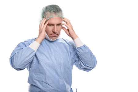 overwrought: Male doctor suffering from a headache and fatigue holding his temples with his hands and eyes closed as he grimaces in pain