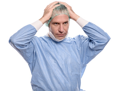 Depressed surgeon in theater garb or scrubs holding his hands to his head with a grim expression isolated on white Stock Photo