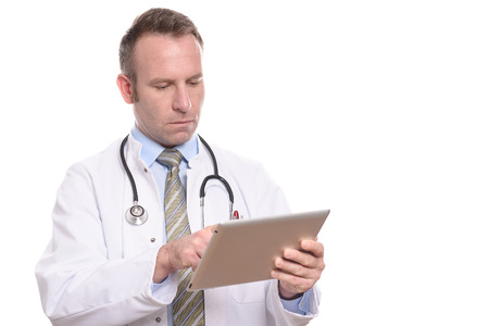 Professional male doctor in a white coat standing consulting a tablet computer reading the information with a serious expression, isolated on white