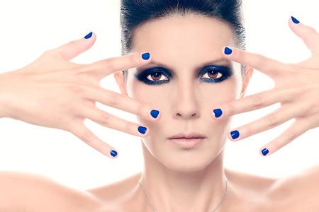 ojos azules: Modelo de manera con azul Esmalte de uñas de cerca sobre fondo blanco Foto de archivo