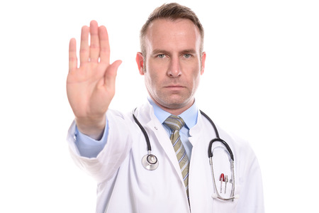 Doctor or male nurse wearing a lab coat holding up his hand in a stop gesture with a stern implacable expression as he prevents access or tells people to halt or go away, isolated on white
