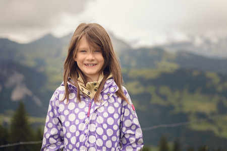 warmly: Warmly dressed pretty little girl wearing a purple floral jacket standing in a field in the mountains looking at the camera with a happy friendly smile.
