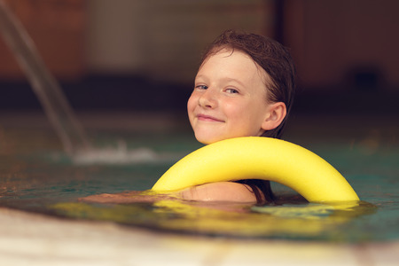flotation: Proud young girl swimming in a pool wearing a bright yellow flotation ring over his shoulder looking at the camera with a playful mischievous grin