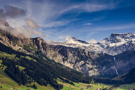 Scenic high altitude mountain landscape with snowy peaks and forested valleys under a cloudy blue sky with tendrils of mist Stock Photo - 31249933