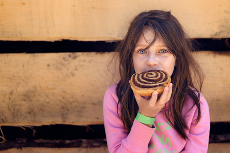 log hair: Brunette Girl with Messy Hair Eating Cinnamon Roll Pastry in front of Log Cabin Stock Photo