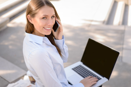 High angle view of a friendly attractive young woman sitting talking on a mobile phone while working on a laptop computer in a communications and mobility concept, outdoors with copy space photo
