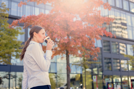 to go cup: Urban Woman Sipping Coffee in To Go Cup in Autumn City Environment with Sun Shining in Background Stock Photo