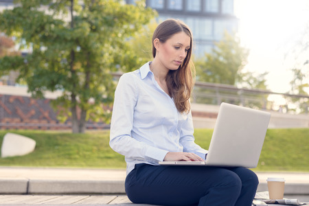 formal clothes: Attractive young woman wearing formal clothes while working outdoor on a laptop, with a wireless connection to the internet, in a nice day of summer