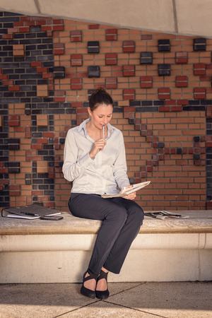 Attractive stylish young businesswoman sitting in a foyer on a bench along a brick wall working on her notes photo
