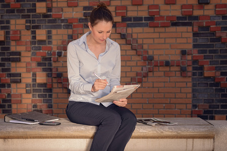 hardworking: Attractive stylish young businesswoman sitting in a foyer on a bench along a brick wall working on her notes