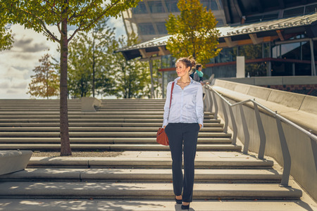 Slender elegant young woman carrying a handbag descending a flight of open-air concrete stairs in town with modern commercial buildings behind her