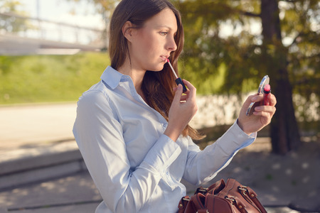 Attractive young woman refreshing her makeup in the street applying lipstick with the use of a small handheld mirror from her large handbag Фото со стока