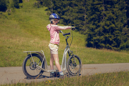 Girl Standing with Kick Bike Scooter and Looking at\ Camera