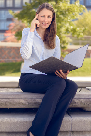 Smiling attractive businesswoman having an idea while reading a business folder in a park photo