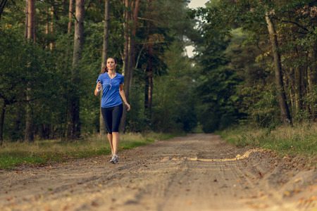 Athletic woman out jogging in a forest approaching the camera along a dirt track through the trees in a health and fitness concept photo