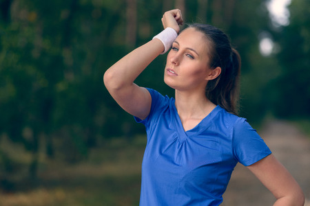 Woman athlete wiping sweat from her forehead onto her wristband as she pauses during her training exercises on a forest track Stock Photo