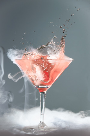 wafting: Smoking martini cocktail in a conical glass with wafting vapour and splashing droplets from a falling cherry for a dramatic effect over a grey background