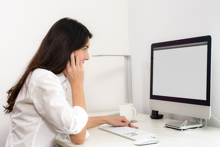 chats: Businesswoman working in her office sitting at a desk in front of her desktop computer with a blank screen visible to the viewer as she chats on her mobile phone, side view Stock Photo