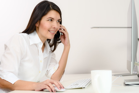 chats: Businesswoman working in her office sitting at a desk in front of her desktop computer as she chats on her mobile phone, side view Stock Photo