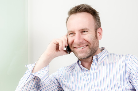 Horizontal portrait of a Caucasian middle-aged handsome man wearing a long-sleeved colorful shirt while having a pleasant conversation on the mobile phone, indoors photo