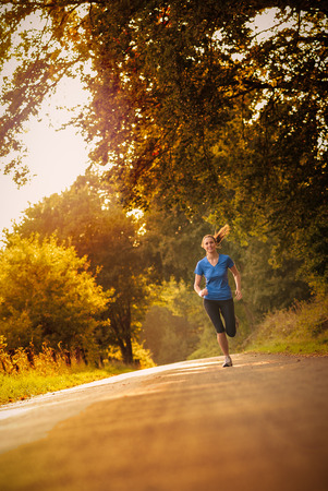 Sporty woman running on a country road beneath leafy green trees approaching the camera as she does her daily exercise and training jogging in the fresh air, low angle, view