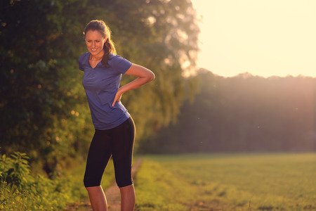 back strain: Woman athlete pausing to relieve her back pain holding her hand to her lower back with a grimace while out training in the countryside with copyspace Stock Photo