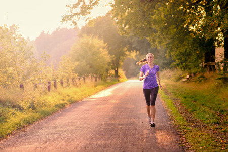 Sporty woman running on a country road beneath leafy green trees approaching the camera as she does her daily exercise and training jogging in the fresh air, low angle, view Stock Photo - 32002537