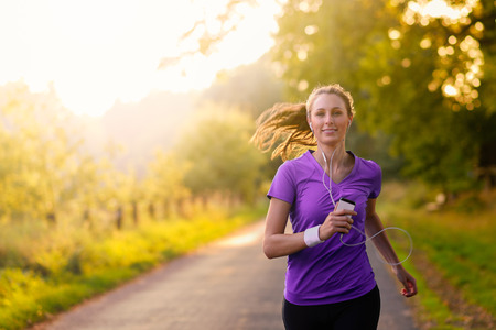 Woman listening to music on her earplugs and MP3 player while jogging along a country road in a healthy lifestyle, exercise and fitness concept Banque d'images