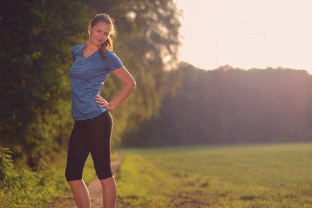throbbing: Woman athlete pausing to relieve her back pain holding her hand to her lower back with a grimace while out training in the countryside with copyspace Stock Photo