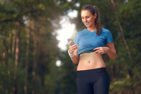 electronically: Young athletic woman out training in the woods standing looking at her smart phone as she uses a mobile application electronically connected to her pulse belt