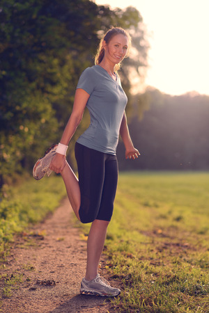limbering: Young woman doing stretching exercises as she limbers up her muscles to go on a jog or begin a workouts standing over a country track in golden light smiling at the camera