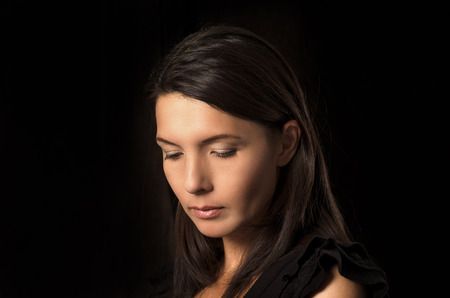 Melancholy depressed young woman with a serious expression and downcast eyes standing thinking in a deep contemplation with her hand to her chin