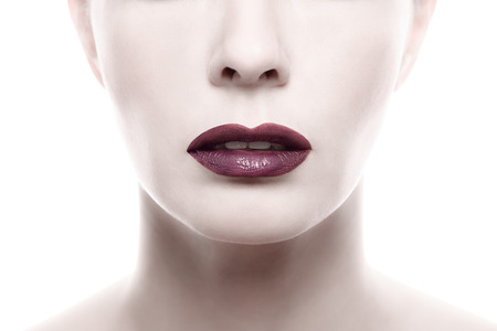 unblemished: Close up Dark Purple Lipstick on Pale Woman Face Isolated on White Background.
